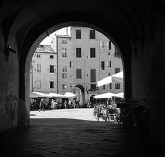 intravedere Lucca (fotomie2009) Tags: lucca piazza anfiteatro arch arco passaggio ombrelloni scorcio toscana tuscany italy italia centro storico monochrome monocromo bw 60