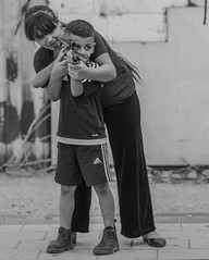 The sergeant and the rookie (ybiberman) Tags: israel jerusalem oldcity alquds muslimquarter boy girl siblings rifle gun people portrait candid streetphotography documentary bw training shooting standing smiling adidas