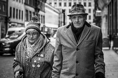 Couple (Leanne Boulton) Tags: urban street candid portrait portraiture streetphotography candidstreetphotography candidportrait streetportrait eyecontact candideyecontact streetlife groupshot old elderly man woman male female face eyes expression mood emotion feeling couple together hat style cold atmosphere weather love companionship tone texture detail depthoffield bokeh naturallight outdoor light shade city scene human life living humanity society culture lifestyle people canon canon5dmkiii 70mm ef2470mmf28liiusm black white blackwhite bw mono blackandwhite monochrome glasgow scotland uk