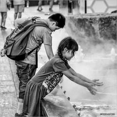 Cool! (John Riper) Tags: johnriper street photography straatfotografie square vierkant bw black white zwartwit mono monochrome singapore candid john riper xt2 fujifilm xf18135 kids water cold steam fun mist
