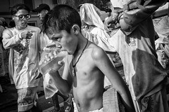 The Mood Of The 9 Emperor - Photo 19 (Mio Cade) Tags: nineemperor festival vegetarian boy men devotee child ritual religion reportage series phuket thailand asia street ceremony monochrome hot water drink firecrackers explode shirtless smoke hurt torture pain presson endurance