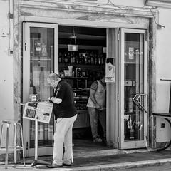 Viareggio 02 (Peter.Bartlett) Tags: square niksilverefex window people newspaper olympuspenf urbanarte poster door streetphotography peterbartlett man urban reflection monochrome doorway m43 microfourthirds cafe bw lunaphoto sign blackandwhite candid noiretblanc viareggio toscana italy