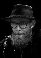 Portrait (D80_547385) (Itzick) Tags: candid copenhagen bw blackbackground bwportrait beard hat man glasess portrait face facialexpression streetphotography denmark d800 itzick