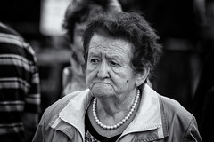 Mother-of-pearl (Frank Fullard) Tags: frankfullard fullard candid street portrait black white blanc noir older lady elderly pearl motherofpearl necklace jewel mother swinford mayo irish ireland serious face expression feile festival heritageday siamsa sraid