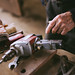 The old man takes an electric drill. Close up of arm and drill.