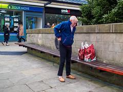 Morley 009 (Peter.Bartlett) Tags: bag shopfront unitedkingdom bench people streetphotography olympuspenf westyorkshire colour peterbartlett man urban candid uk m43 microfourthirds sign leeds england