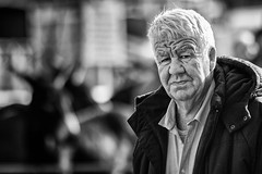 Chiselled face. (Frank Fullard) Tags: frankfullard fullard candid street portrait watching face expression lined black white blanc noir monochrome ballinasloe galway horsefair fair festival heritage irish ireland frown serious