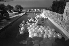 Pool Party  (Tri-X) (Harald Philipp) Tags: hotel pool balloons party swimmingpool saniclub view holiday vacation tourism tourist destination travel adventure wanderlust beautiful atmosphere haraldphilipp outdoors rural scenic scenery landscape seascape sea bay water waterfront beach blackandwhite bw blackwhite monochrome schwarzweiss nocolor dark contrast kodak trix 35mm 135 iso400 film grain analog filmphotography selfdevelop homedevelop ufg nikon nikkor slr fm3a antiquecamera nikon5000ed coolscan greece kassandria europe european mediterranean aegean