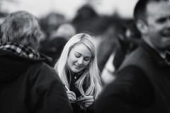 Take a note (Frank Fullard) Tags: frankfullard fullard candid street portrait lady blonde black white blanc noir monochrome monocrome ballinasloe galway fair horsefair pen note write writing smile oldfashioned