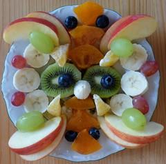 Obstgesicht / Fruit face (ursula.valtiner) Tags: obst fruits mandala obstmandala mandalaoffruits äpfel apples bananen bananas heidelbeeren blueberries weintrauben grapes kakis persimmon kiwis mandarinen mandarins pareidolia früchte essen food