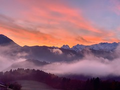 Dawn over Zahmer Kaiser mountains seen from Breitenau near Kiefersfelden, Bavaria, Germany (UweBKK (α 77 on )) Tags: dawn morning sun sunrise sky cloud red pink mist fog mountain range tree forest outdoors nature zahmerkaiser zahmer kaiser kaisergebirge breitenau kiefersfelden bavaria bayern germany deutschland europe europa iphone autumn autumnal fall herbst landscape landschaft scene scenery scenic view