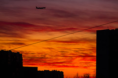 Sunset in the city in freezing weather (psvrusso) Tags: sunset silhouette city sky urban outdoor dawn orange cityscape view town building plane air clouds airplane fly aircraft jet
