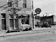 The Watering Hole: Saloon in the stockyards district. South Omaha, Nebraska, November 1938. (polkbritton) Tags: johnvachon 1930s fsaowi libraryofcongresscollections nebraskahistory streetphotography classiccars