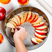 Woman lays slices of apples on a baking sheet. Home cooking concept