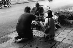 Almsgiving (D. R. Hill Photography) Tags: bangkok thailand thai asia southeastasia capital urban city street streetphotography documentary candid film analog analogue 135 35mmfilm grain monochrome blackandwhite monk alms culture religion buddhist buddhism contax contaxg1 g1 zeiss carlzeissplanar45mmf2 45mm planar primelens fixedfocallength almsgiving merit