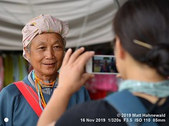 2016-03a Photographing Photographers 2019 (05c) (Matt Hahnewald) Tags: matthahnewaldphotography facingtheworld qualityphoto people head face mouth lips betelstainedlips betel betelleaf expression lookingatcamera consensual candid conceptual diversity working travel ethnic tribal minority hilltribe local rural traditional cultural market village photographer maesariang maehongsonprovince northern thailand asia asian thai karen japanese person two female elderly old woman women photography portraiture primelens nikond610 nikkorafs85mmf18g 85mm 4x3ratio resized 1200x900pixels horizontal street portrait doubleportrait halflength closeup seveneighthsview depthoffield outdoor colour posingcamera authentic smiling photographing iphone rieshiina takingphoto