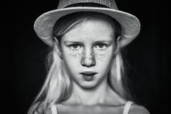 Girl with hat (B&W edit) (PascallacsaP) Tags: hat portrait 35mm ambientlight naturallight portraiture freckles frontal speedmaster windowlight f095 seriouslook captureonepro windowlighting mitakon zhongyimitakonspeedmaster35mmf095markii blackandwhite bw monochrome staring bokeh shallowdof shallowdepthoffield yourbestshot2019