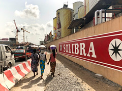 Côte d'Ivoire, Abidjan - In the divide between beer and driving - March 2019 (Cyprien Hauser) Tags: street road drink junction côte divoire ivory coast africa abidjan treichville beer solibra castel women traffic cars way walking head loincloth wax brewery industry plant beerhouse carrying