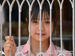 2019-03a Burma (41b) (Matt Hahnewald) Tags: facingtheworld matthahnewaldphotography people face hair bigeyes eyes head expression fringe bangs beautifuleyes dollface consensual lookingatcamera qualityphoto beauty asian asia burma lifestyle grace exotic myanmar local emotional oriental ethnic cultural shanstate kalaw girl female person one young teen portraiture burmese primelens street portrait horizontal closeup 85mm resized nikkorafs85mmf18g 4x3ratio nikond610 1200x900pixels colour cute beautiful pretty hand looking outdoor availablelight feminine posing headshot lovely fullfaceview smilingmouthclosed behind eyeliner burglarbars securitydoor symbol