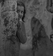 Actually, she was, simply, playing hide & seek with her friend... (ybiberman) Tags: israel jerusalem oldcity alquds christianquarter viadolorosa girl playing hideandseek hide peep missingteeth portrait streetphotography documentary games streetgames braids ethiopian hideandgoseek hider