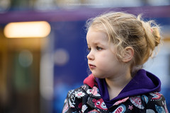 Child in Train Station (Steven Robinson Pictures) Tags: girl cute train trainstation nikon85mmf14d nikond810 portrait shallowdepthoffield bokeh beautiful innocence child blonde cold jacket looking staring eyes focus people lights