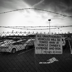You will be towed if you do not follow the rules...see arrow (romeos115) Tags: parking cars sign wire barbed monochrome bw arrow lot