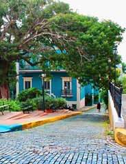 Historical Hues (brucecarlson66) Tags: history historical old san juan puerto rico blue cobblestone century centuries green tree garden bench walk woman fence window home color colorful hue lamp branch frame house life island united states territory walkway white trim red brick