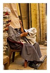 Les nouvelles sont-elles bonnes ? (Marie Hacene) Tags: egypte assouan journal quotidien caché homme lecture rue rideau street