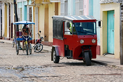 The Red Baron (without wings 😉) (emerge13) Tags: architecture colonialarchitecture cuba people vehicles bici bicycles bikes motorbikes trinidadsanctispirituscuba architecturaldetails humans candid cobblestonestreets trinidad street streets colorfulcities transportation