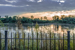 Sunrise Along the Riverfront (asonyphotographer) Tags: leavenworth kansas unitedstatesofamerica sunr sunrays golden overcast fence weeds trees woods water river missouririver riverfront sony ilca77m2 morning goldenhour tamron inexplorer explore