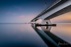 The Water Is Always Deeper Than What It Reflects II (Alec Lux) Tags: m15 architecture blue bluehour bridge coast coastline curves design exterior golden goldenhour haida haidafilters holland lines longexposure minimal minimalism modern netherlands ocean outdoor outside reddiamond reflection sea seascape shape sun sunset symmetry zeeland