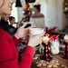 Young beautiful woman with red Christmas sweater drinking coffee with friends.