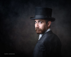 Man in a Suit (saraghedina) Tags: serious moody studiolight painterly horizontal beard hat 50mm canon onelight chiaroscuro suit texture foggy darkbackground oneperson portrait man
