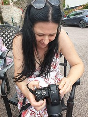 Nina - Tourist with a camera at Blarney Castle (sean and nina) Tags: nina camera tourist tourism blarney castle county cork ireland irish eire eu europe european woman female girl lady girlfriend fiancee wife married brunette long dark hair sunglasses white summer dress july 2019 stunning cute beauty beautiful gorgeous charm charming candid outddor outside street cafe sitting seated neck throat arms tan tanned skin bare hands face portrait serb shoulders