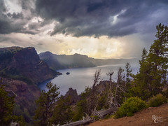 Summer Storm Over Crater Lake (RobertCross1 (off and on)) Tags: 1250mmf3563mzuiko cascaderange cascades craterlake craterlakenationalpark em5 klamath nps omd or olympus oregon pacificnorthwest cliffs clouds lake landscape mountain mountains rain storm thunderstorm trees volcanic volcano water