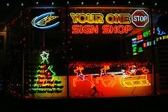 One Stop Sign Shop - Fox Lake, Illinois (Cragin Spring) Tags: foxlake foxlakeil foxlakeillinois night lights illinois il lakecountyil unitedstates usa unitedstatesofamerica neon neonsign sign reindeer santa sleigh stopsign store window signshop onestop