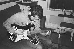 mju - ryan learns guitar (johnnytakespictures) Tags: olympus mju mju1 compact compactcamera film analogue automatic generalphoto surv27dp superpanchromatic surveillance monochrome blackandwhite bw expiredfilm expired ryan brother boy teenager man guitar guiatarist music musician learning playing play house home
