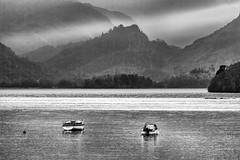 A shaft of sunlight hits land behind Castle Crag (Iand49) Tags: derwentwater lake keswick cumbria england europe lakedistrict thelakes boats castlecrag fell moody atmospheric monochrome blackandwhite landscape stormy gloweringskies darkclouds shaft sunlight november autumn trees threatening riggedscenery dramatic nature outdoor tourism travel holidays fellwalking rambling hiking rural countryside water