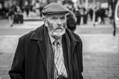 A Long Winter (Leanne Boulton) Tags: urban street candid portrait portraiture streetphotography candidstreetphotography candidportrait streetportrait eyecontact candideyecontact streetlife old elderly man male face eyes beard cap expression emotion mood feeling cold winter tone texture detail depthoffield bokeh naturallight outdoor light shade city scene human life living humanity society culture lifestyle people canon canon5dmkiii 70mm ef2470mmf28liiusm black white blackwhite bw mono blackandwhite monochrome glasgow scotland uk