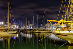 Port Vell - by night (Fnikos) Tags: port porto puerto harbour harbor portvell city construction building architecture tower bridge rambla sea mar mare serene seascape water waterfront sky cielo skyline cloud clouds boat ship sailboat color colour colores colours colors light lights reflections shadow shadows nature naturaleza natura natur tree palmtree night nightview nightshot longexposure outside outdoor