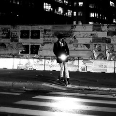 Behind the headlight (pascalcolin1) Tags: homme man trottinette scooter nuit night lumière light passagepiéton crosswalk cigarette casquette cap photoderue streetview urbanarte noiretblanc blackandwhite photopascalcolin 50mm canon50mm canon