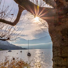 Into the Light (ivanstevensphotography) Tags: boats water lake trees plants foliage sunstar clouds mountains