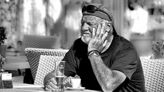 When the sun is hot and the beer is cold. (Neil. Moralee) Tags: neilmoralee man beer drink old alcohol hat sunshine mature wrinkles sunlight black white mono monochrome blackandwhite blackwhite neil moralee bw blackbackground candid olympus omd em5 cafe street sunglasses tired beard stubble watch coffee cyprus paphos pafos waiting sleepy resting face portrait bright brite