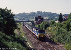 Lazy, Hazy Days in Devon (Kernow Rail Phots) Tags: 47583 countyofhertfordshire class47 474 nse networksoutheast seatonjunction seaton junction closed station footbridge bridges buildings trees countryside rural summer hazy sun nselivery 1622 exeterstdavids exeter waterloo wednesday 10th june 1992 mk2 coaches stock singletrack train trains railway railroad railways 1990s 1987 revised network southeast livery 1061992 devon britishrail br ex southern region duff brush type4
