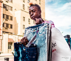 The New Yorkers - Dry-cleaner duty (François Escriva) Tags: street streetphotography us usa nyc ny new york people candid photo rue sun light woman colors sidewalk manhattan sky clouds clothes garment grimace funny face jeans denim blue hair red