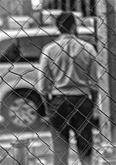 Beyond the Fence (nrhodesphotos(the_eye_of_the_moment)) Tags: dsc99433001084 wwwflickrcomphotostheeyeofthemoment theeyeofthemoment21gmailcom beyondthefence man candid streetscene manhattan nyc auto reflections shadows monochrome outdoors metal midtownnyc transportation person pedestrian blackandwhite wheels urban