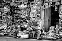 The ToyStore (MartinGerbrandy) Tags: funny asphalt boxes sitting salesmn oneperson person white black blackandwhite manualfocus travel fujinon fuji streetphotography toystore toys toy hanoi people vietnam