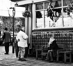 Smoking (f22photographie) Tags: cigarettesmoking women womensmoking streetphotography building pub talking urban culture lifestyle people bench sitting blackandwhite monochrome windows pavement streetfurniture gritty