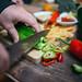 Man hands cutting fresh green pepper on wooden board overhead top view.