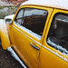 Old yellow VW Beetle car with white stripes under snow in rare snowy day in winter.